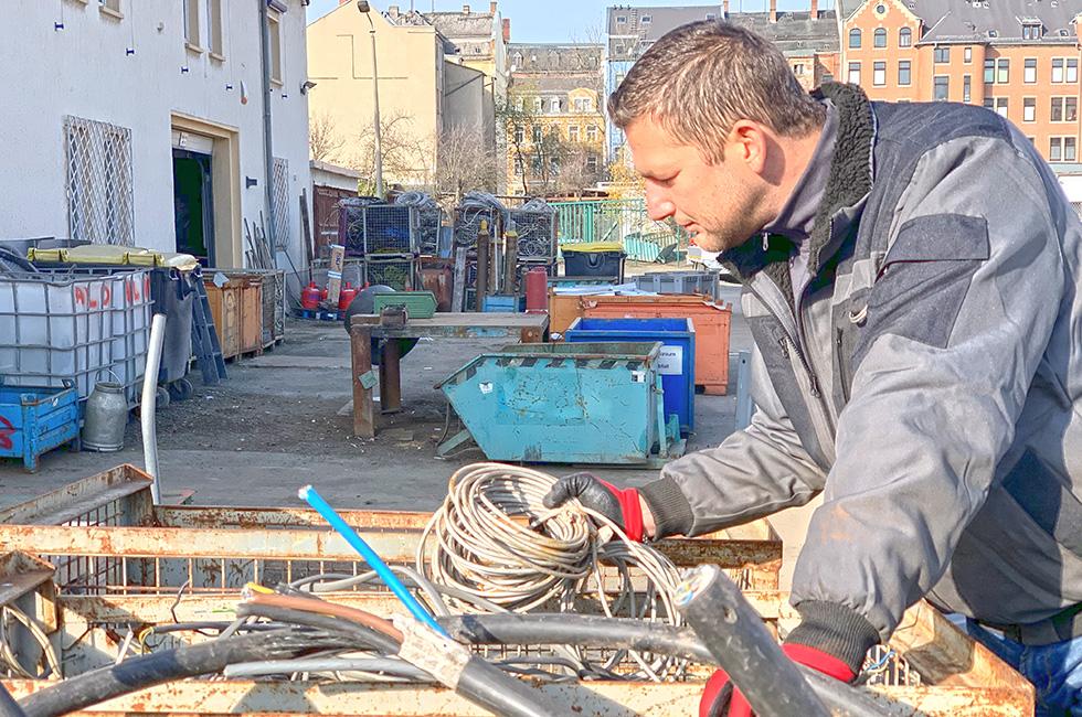 Schrotthändler Robert Wittig schaut prüfend in eine Sammelbox voller Kupferkabel. foto: sebastian höfer
